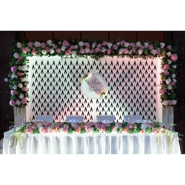 Арка с цветами за столом молодоженов